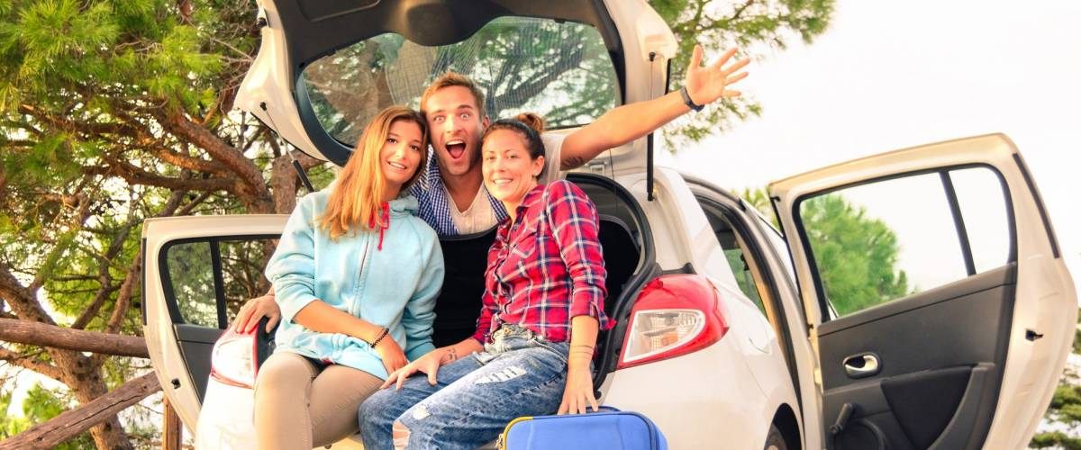 Three best friends travelers put hands sitting in the car. Young relaxing hipster wanderers enjoying exclusive alternative destination. Tourist with luggage are ready for holiday life moment.