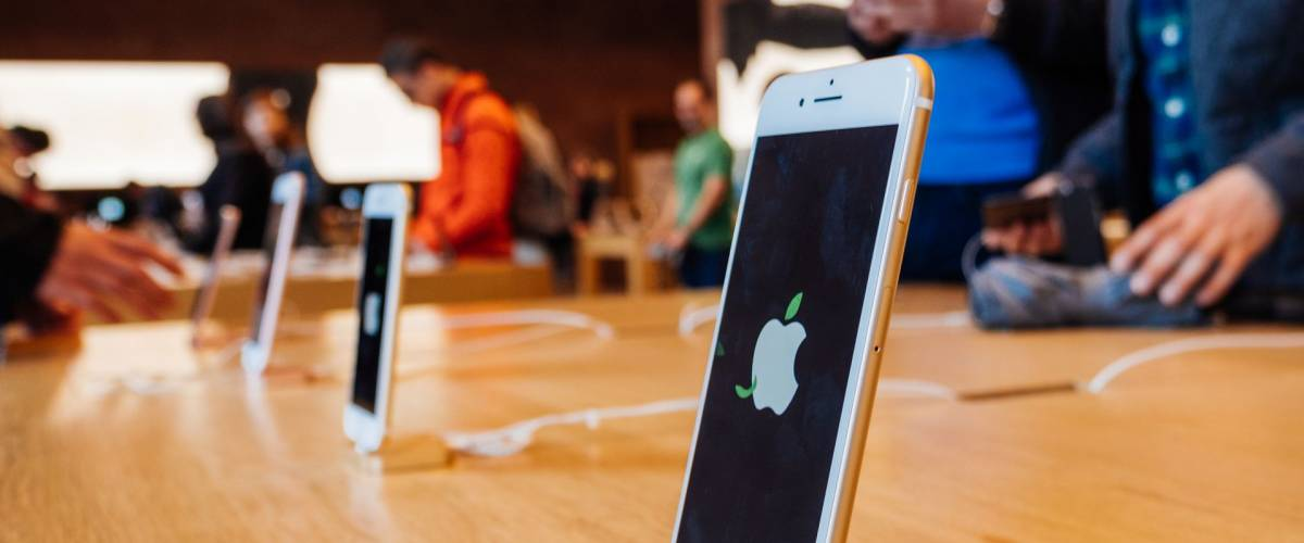 STRASBOURG, FRANCE - APR 27, 2016: Latest iPhone 7 and iPhone 7 Plus in Apple Store with screensaver dedicated to Earth Day  - customers shopping testing in the background