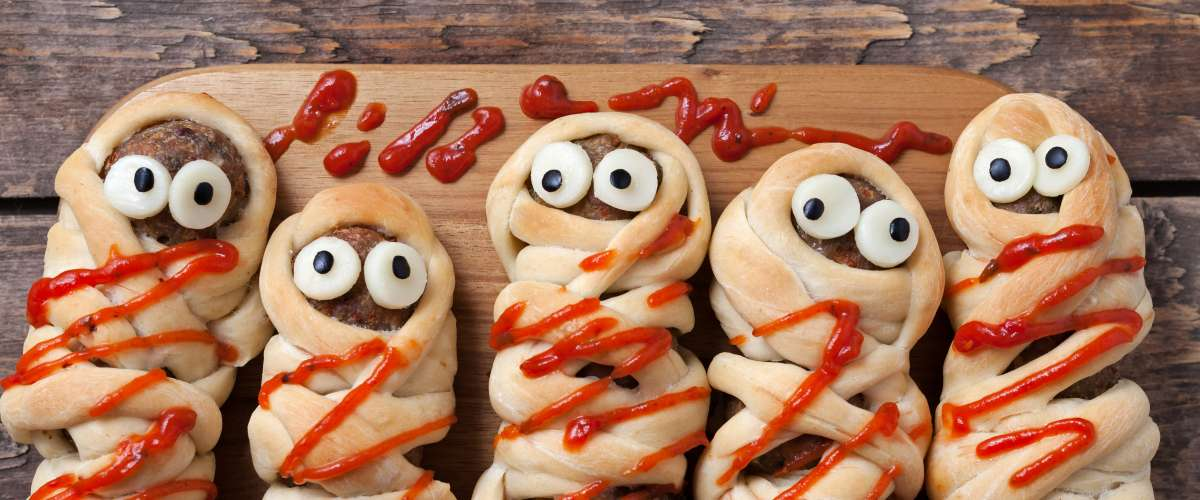Halloween homemade food sausage meatball mummies wrapped in dough, baked and covered with fake blood sauce