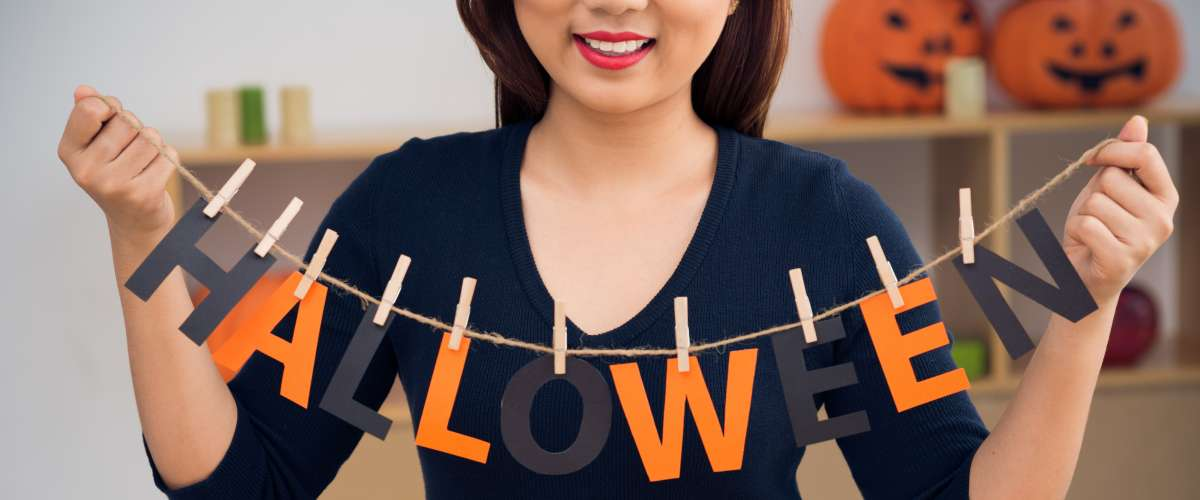 Cropped image of woman with word Halloween hanging on clothesline