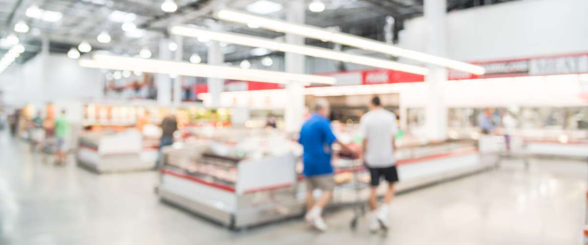 Blurred image customers shopping for fresh raw beef, pork, chicken, fish at meat department in wholesale store in US.
