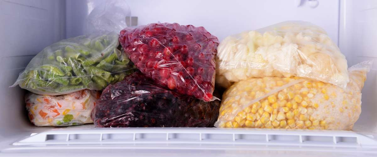 Frozen berries and vegetables in freezer at home