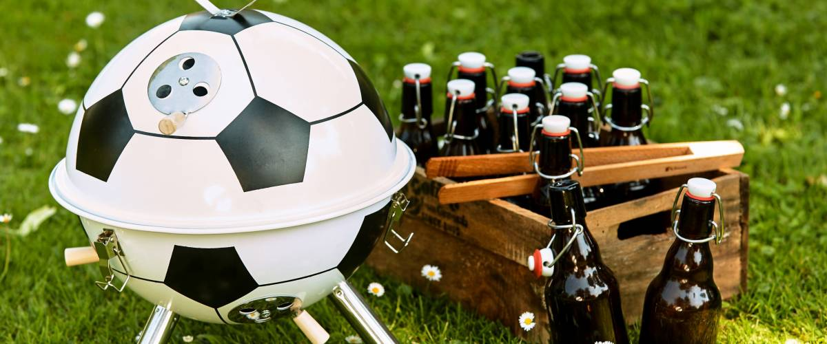 Themed soccer ball shaped BBQ standing outdoors in a spring meadow alongside a crate of beers ready for a celebratory party