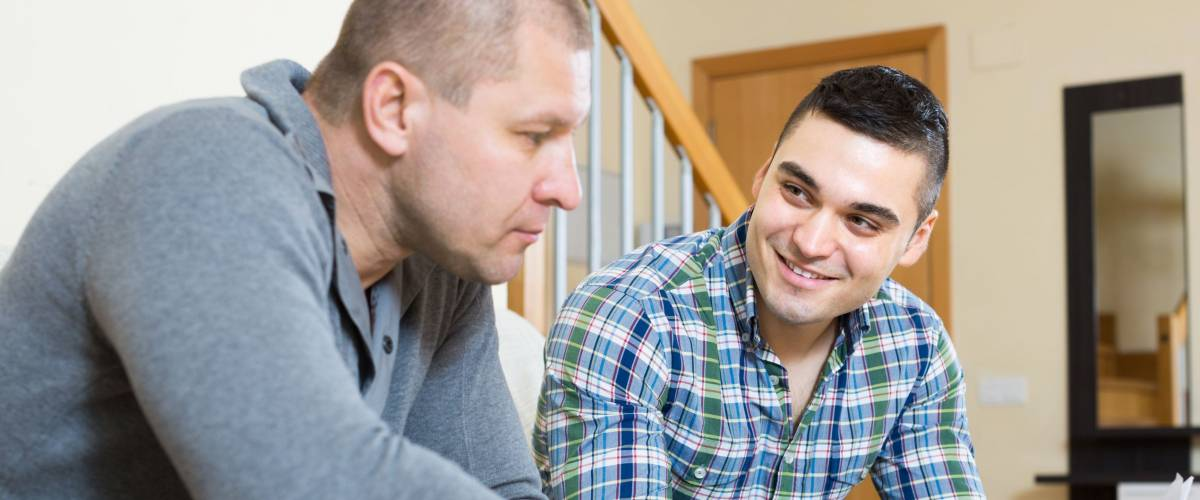 Adult smiling man helping friend to fill banking document indoor