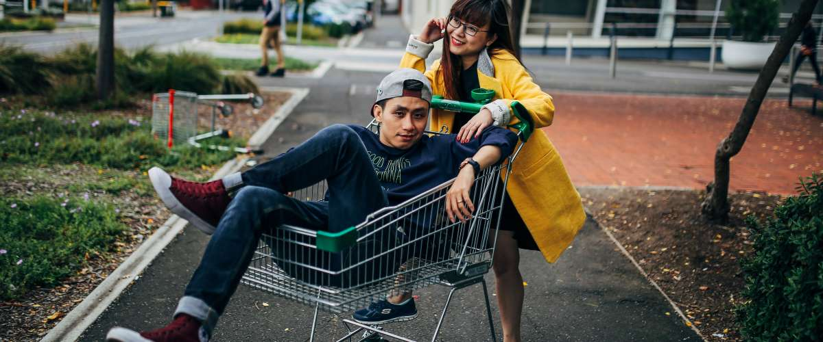 young woman pushing young man in shopping cart