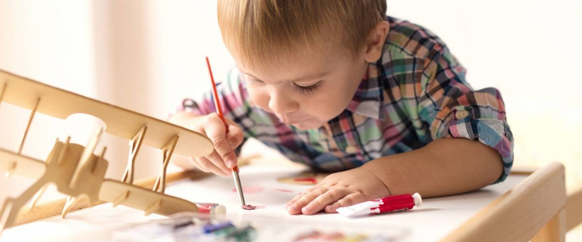 Adorable kid playing on his table with watercolors, painting a wooden parts of his airplane wooden toy. He is young designer with many ideas waiting to be found. Very shallow depth of field.