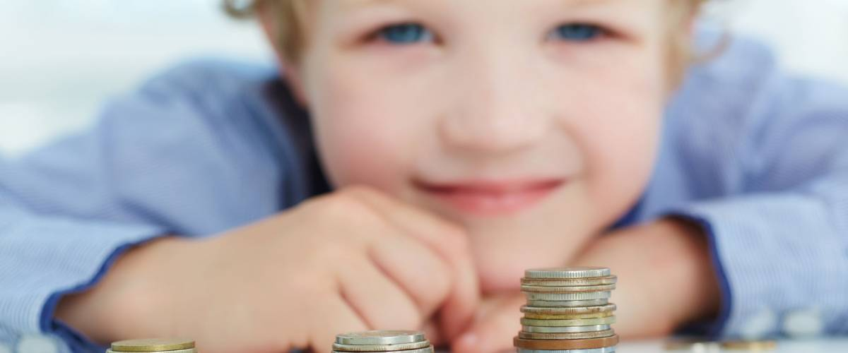 Young boy build a tower by coins. The concept of children's economic education.