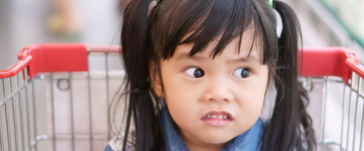 Asian children cute or kid girl wearing jeans with funny and joke or shocking face for sale price with sit in the supermarket cart at market