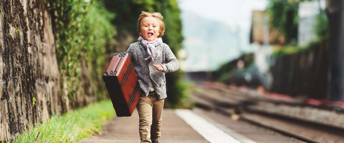 Outdoor portrait of cute little kid boy, run to the train station, wearing beige jacket, trousers, scarf and brown retro shoes, holding old vintage suitcase