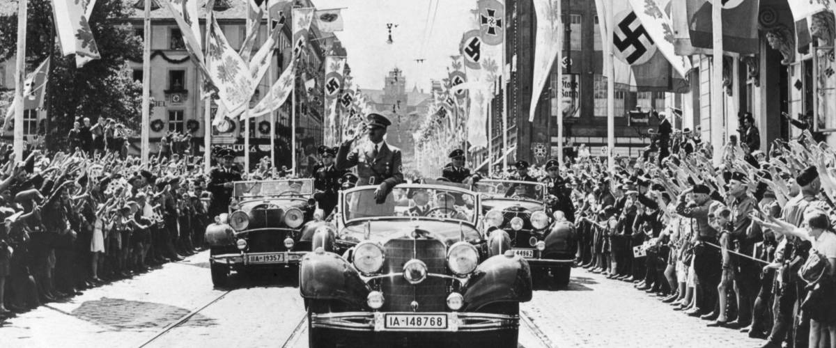 Adolf Hitler waving to crowds from his car at the head of a parade. The streets are decorated with various swastika banners. Ca. 1934-38. Location is unidentified.