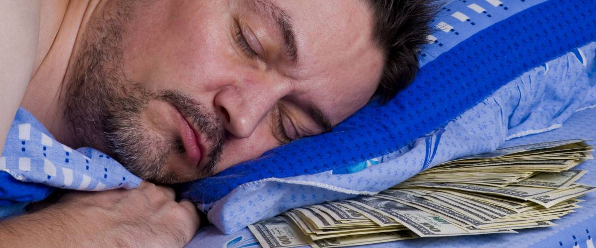 man sleeping with money under his pillow