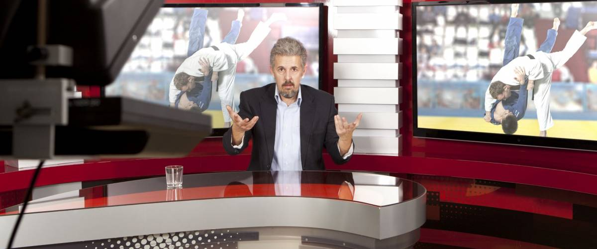 Sports News. A television anchorman at studio during live broadcasting