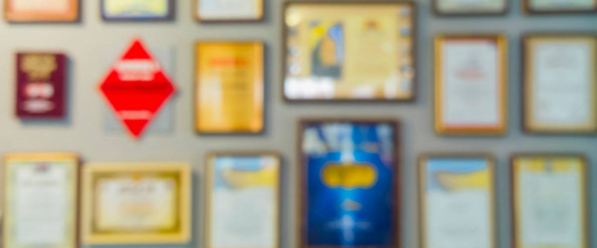 Certificates and diplomas in frames on the wall. Abstract blurry image.