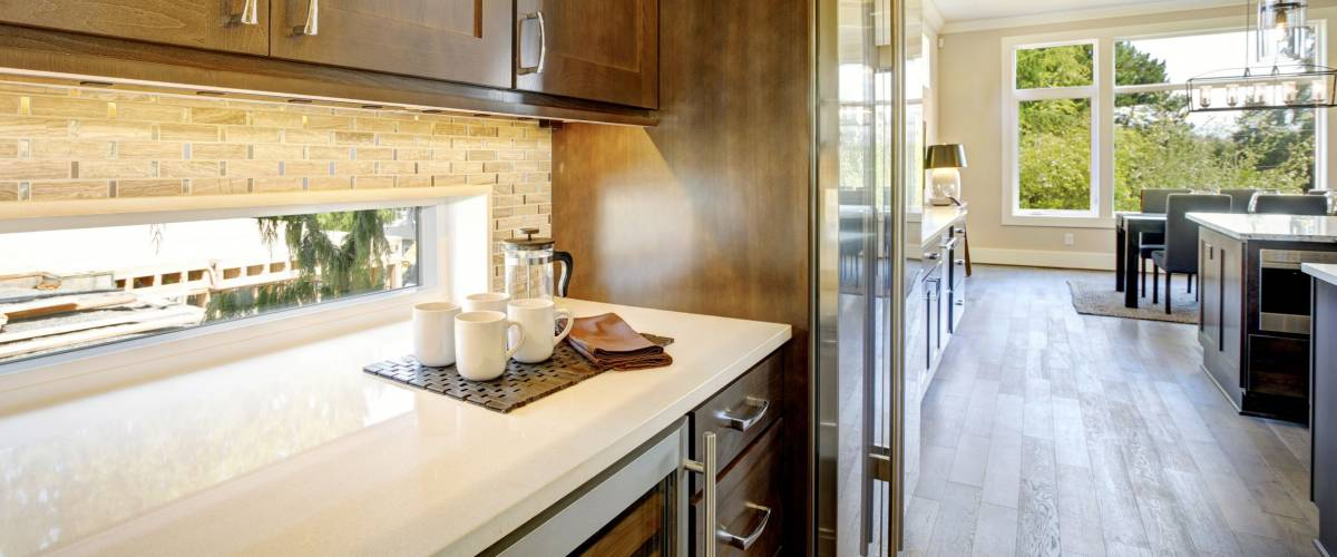 Luxury kitchen features brown wood front upper cabinets and shaker lower cabinets