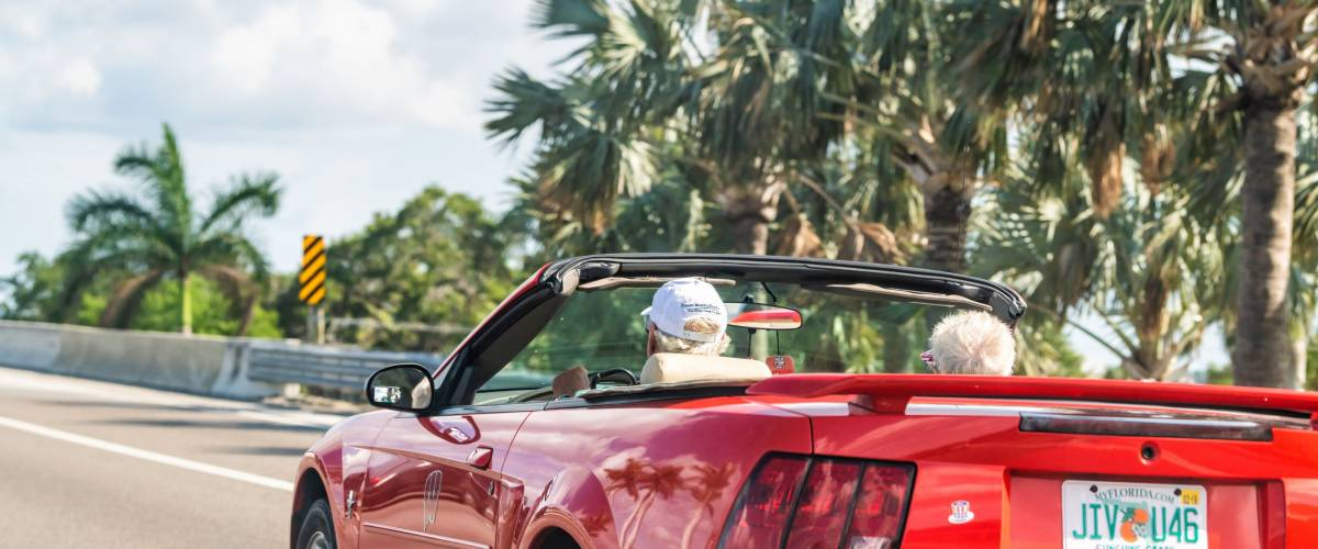 Ellenton, USA - April 27, 2018: Senior couple driving on sports car on road, highway with palm trees in Florida