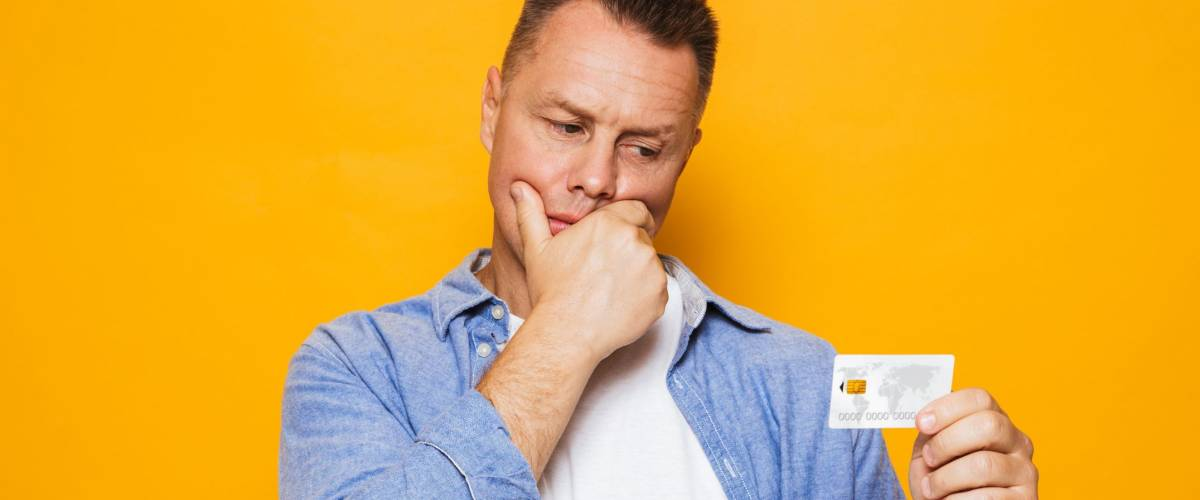 Portrait of a doubting middle aged man holding credit card isolated over yellow background