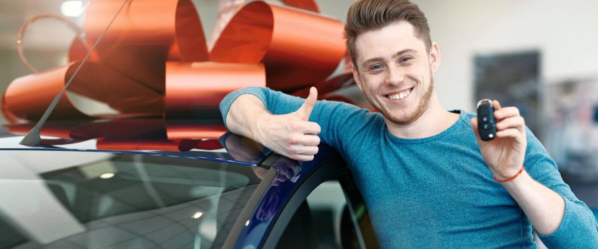 Happy car owner is showing thumbs up and his new car key.