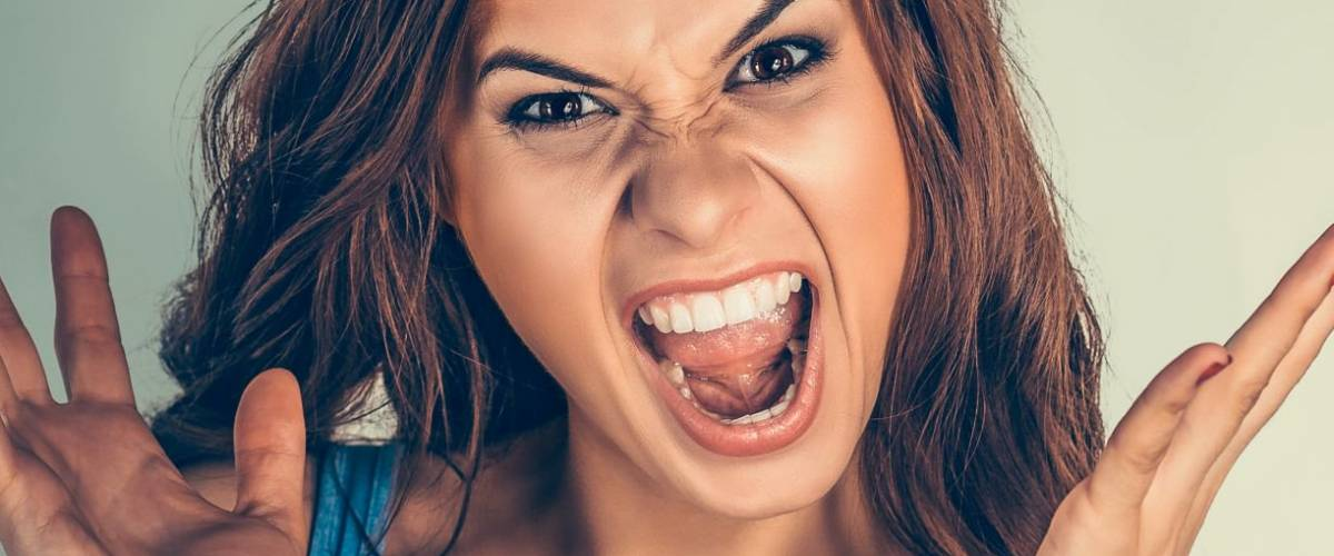 Close up very angry woman screaming in horror, grimace portrait.