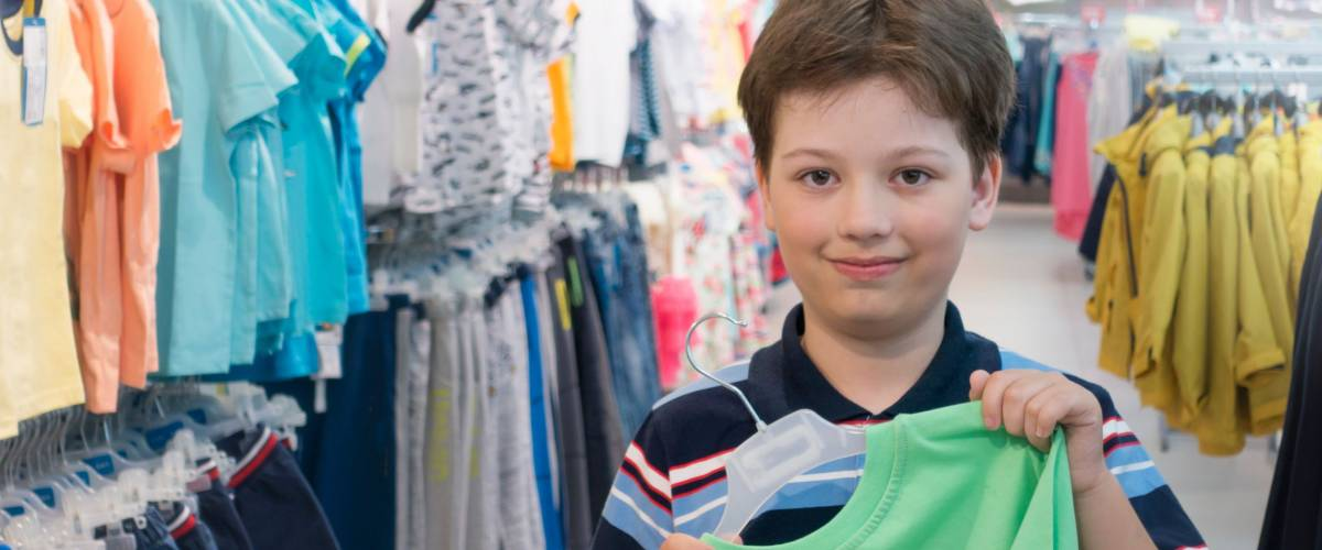 boy chooses clothes in the store, new t-shirt hands of the child