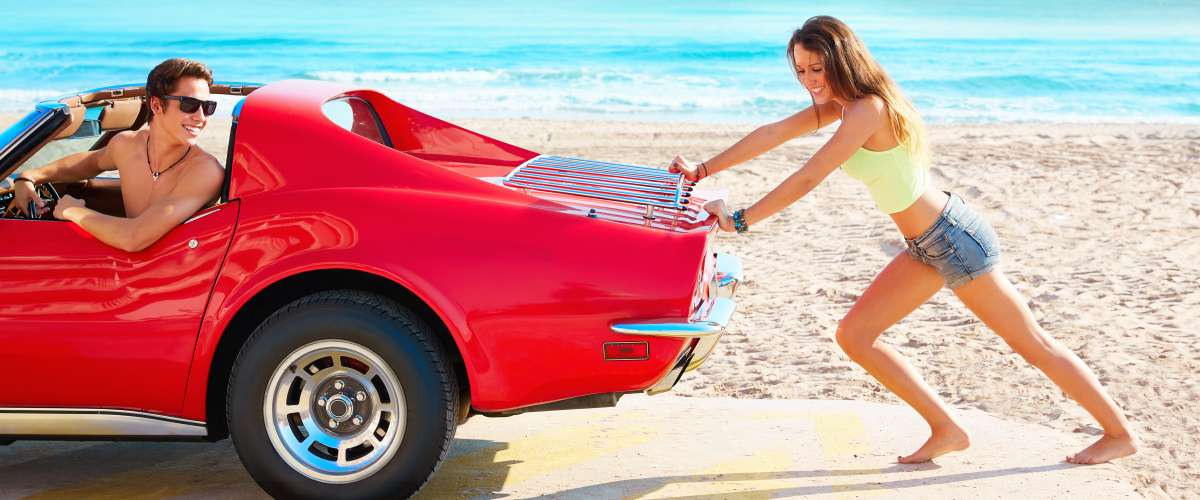 young couple pushing a convertible on the beach