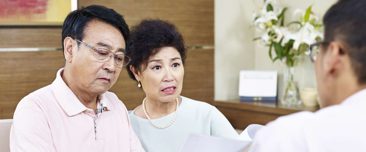 senior asian couple shocked at bank paperwork
