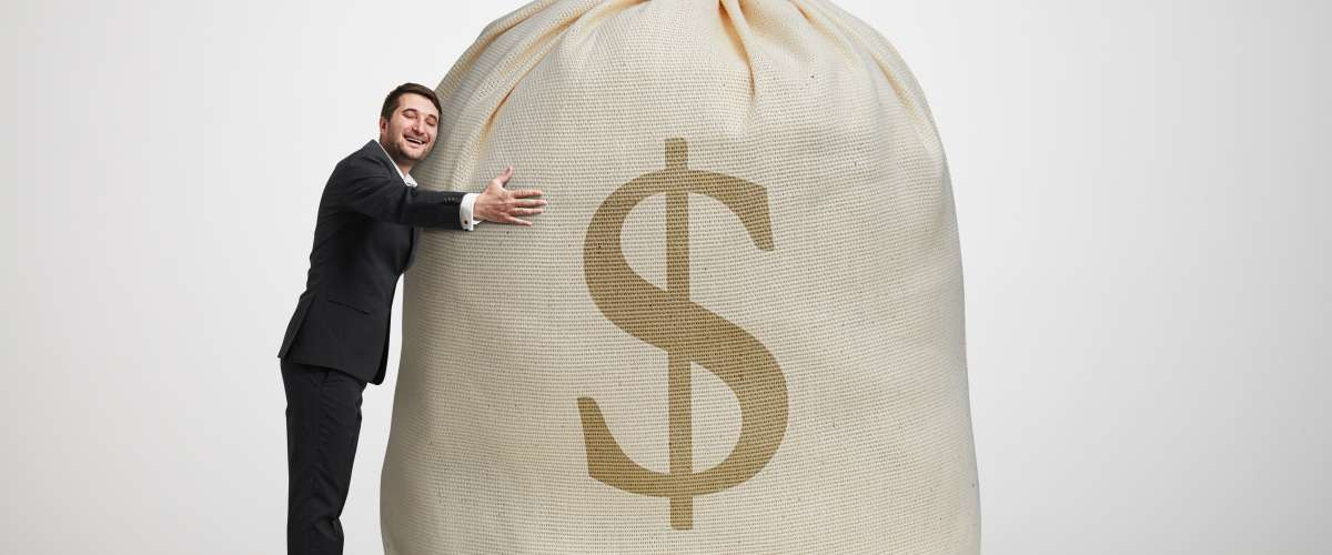 man hugging a large bag of money