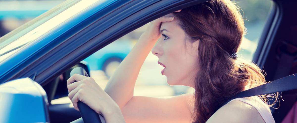 Side view window portrait displeased stressed angry pissed off woman driving car annoyed by heavy traffic