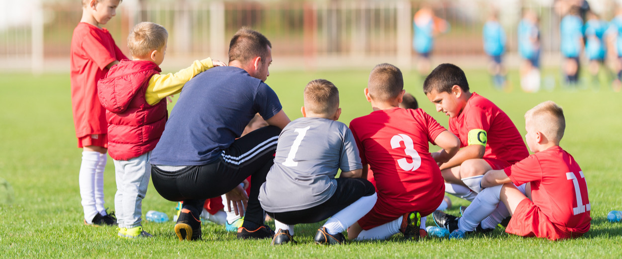 Young man coaching kids soccer
