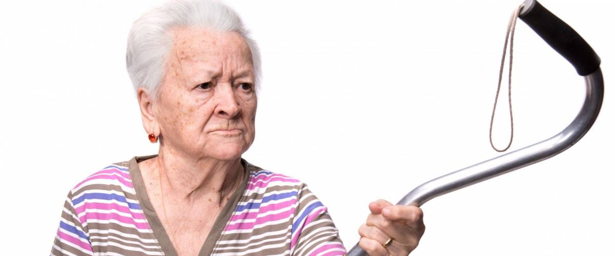 Old angry woman threatening with a cane on a white background
