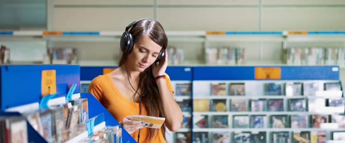 caucasian woman with headphones, choosing cd in music shop. Horizontal shape, front view, waist up, copy space
