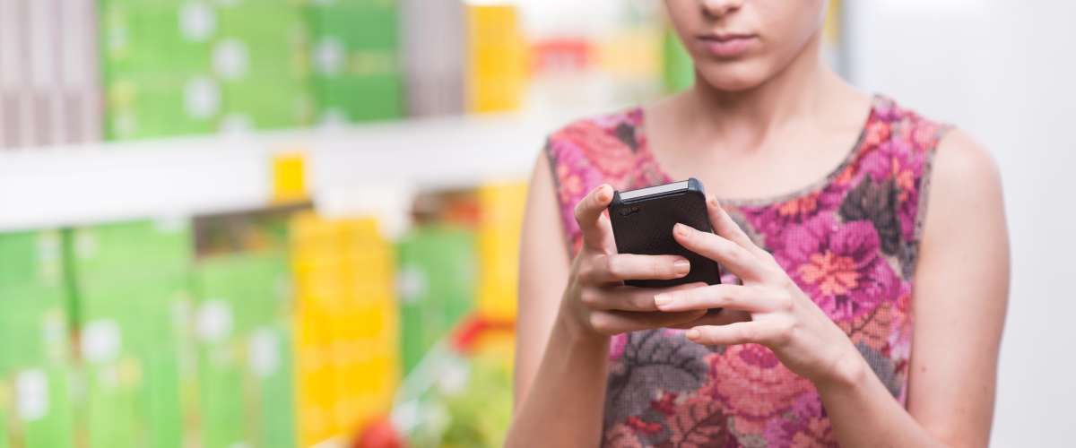 woman using phone to check price in store