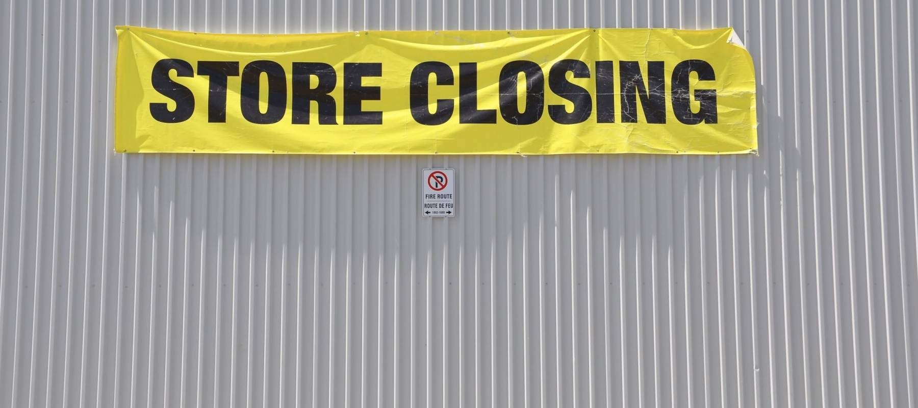 Store closing sign hanging on the concrete wall
