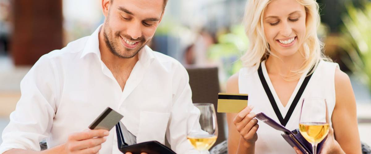 date, people, payment and financial independence concept - happy couple with credit cards in wallets and wine glasses paying bill at restaurant