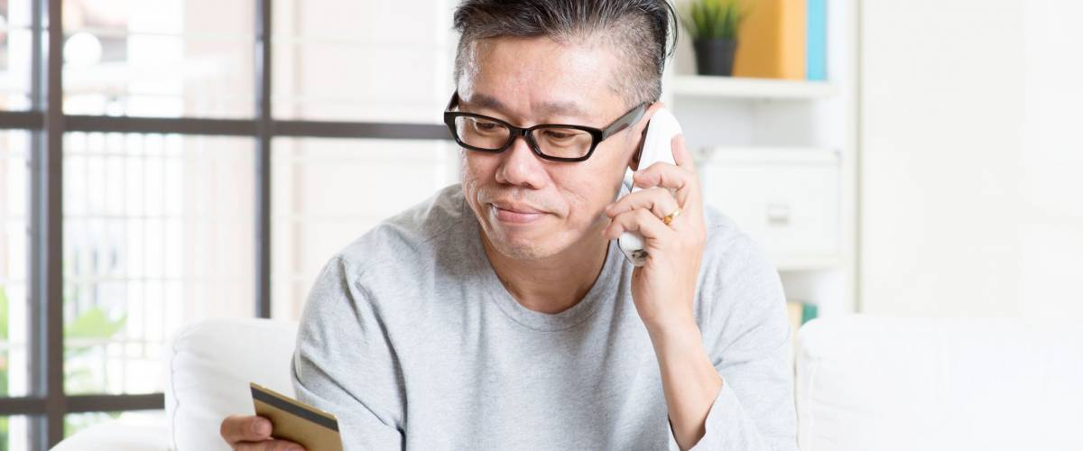 Asian mature man making order by phone, looking at credit card, and using laptop computer at home.