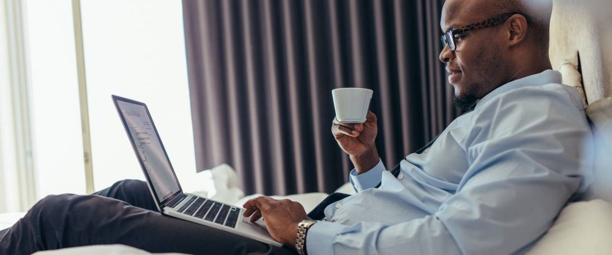 Man in formal clothes working on laptop while lying in bed. Businessman working on laptop computer while drinking coffee in his hotel room.