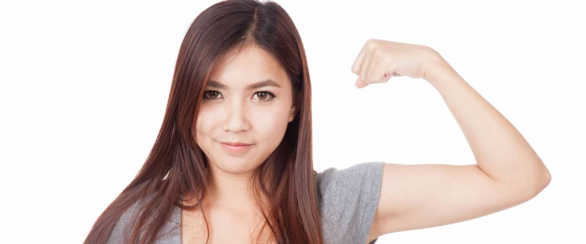 Young Asian woman flexing her biceps  isolated on white background