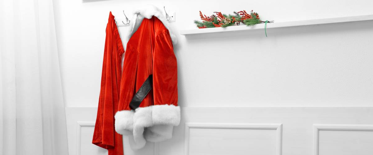Santa costume hanging on white wall background