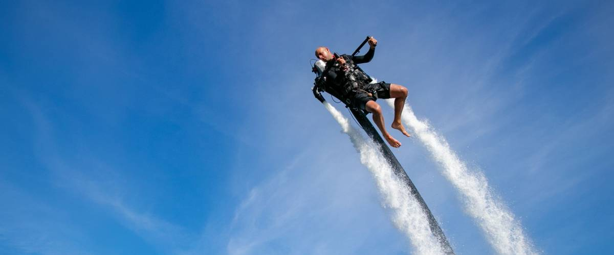 Thrillseeker, man, athlete strapped to Jet Lev, levitation soars into a blue sky with wispy clouds