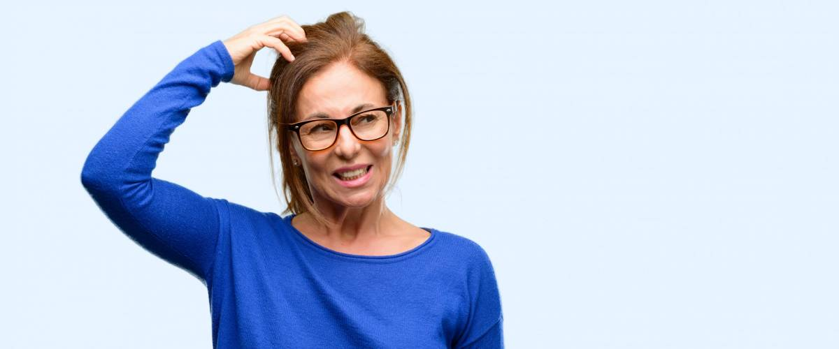 Middle age woman wearing wool sweater and glasses doubt expression, confuse and wonder concept, uncertain future isolated blue background