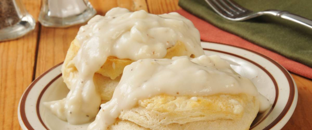 Fresh baked biscuits with country gravy on a rustic wooden table.