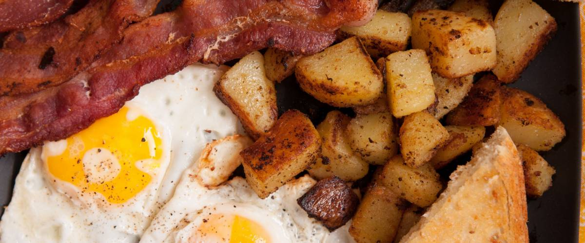 Bacon and eggs with toast and home fries.