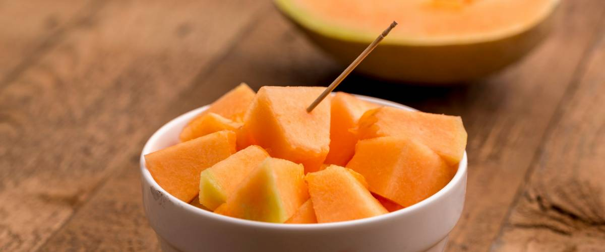 freshly cut muskmelon cubes in a white bowl with stick