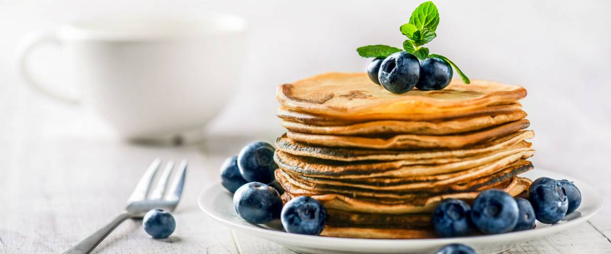 Pancakes with blueberries and mint leaf on top. Pile of small homemade pancakes with forest fruits. Heap of flat thin cake in background.
