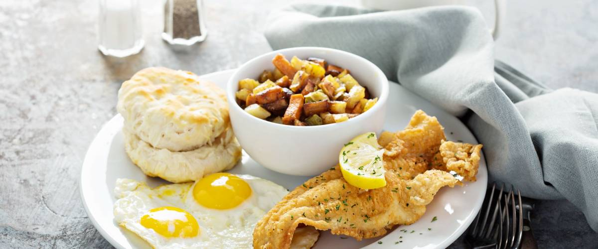 Fried fish breakfast with sunny side up eggs, biscuit and potatoes