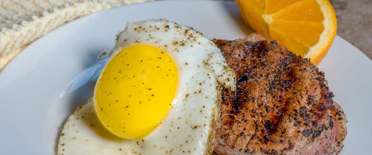 Savory Steak topped with a Sunny Side Up egg cooked to perfection. An orange garnish brings out the beauty of the dish