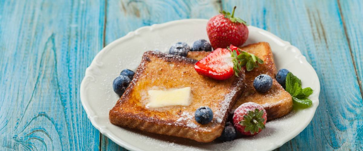 Traditional, delicious, sweet French toast with fruit and butter.