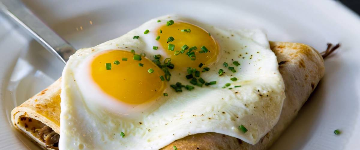 Potato Crepes with baked sunnyside eggs chives breakfast dish