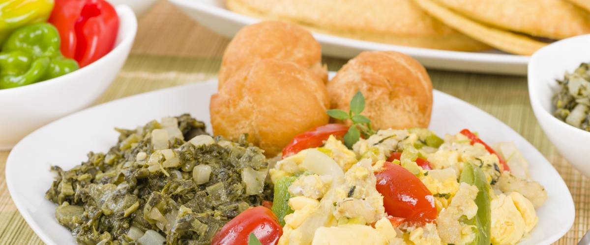 Traditional Jamaican dish made of salt cod and ackee fruit. Served with callaloo and johnny cakes. Patties on background.