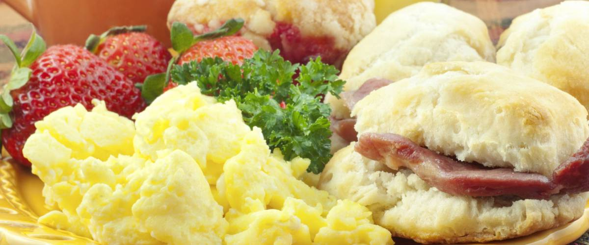 A homemade country ham breakfast with scrambled eggs and ham biscuits