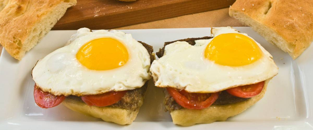 Scrapple and sunny side up eggs on a split hoagie roll with extra bread on a wooden cutting board in background